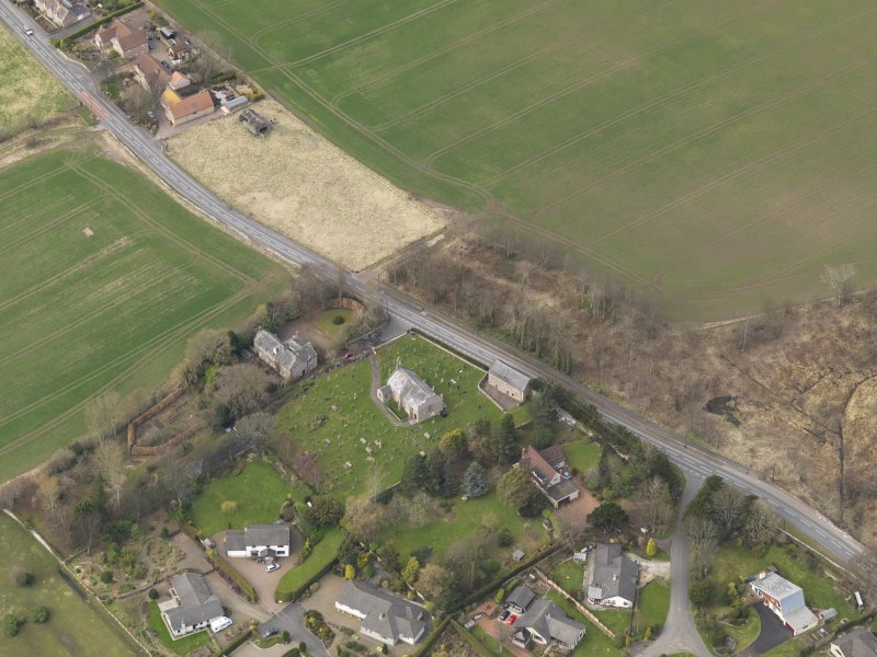 Oblique aerial view centred on the church with the tithe barn adjacent, taken from the SE.