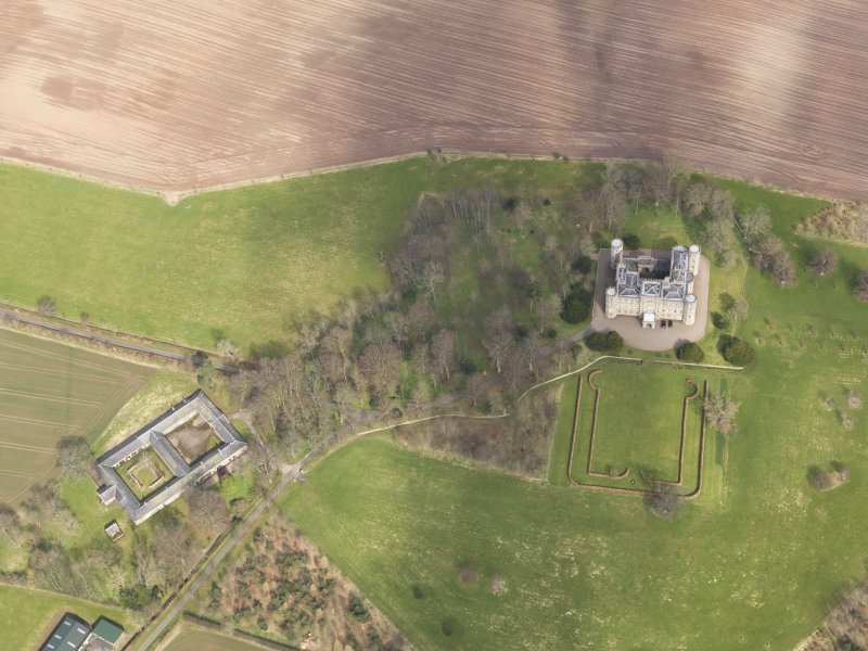 Oblique aerial view centred on the country house with the Home Farm adjacent,  taken from the SW.