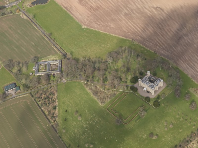 Oblique aerial view centred on the country house with the Home Farm adjacent,  taken from the SSW.