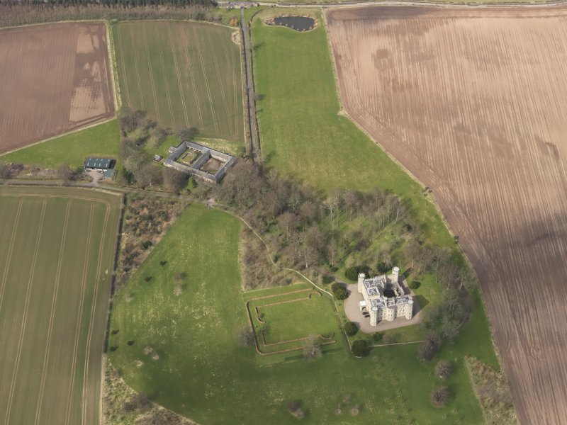 Oblique aerial view centred on the country house with the Home Farm adjacent,  taken from the SSE.
