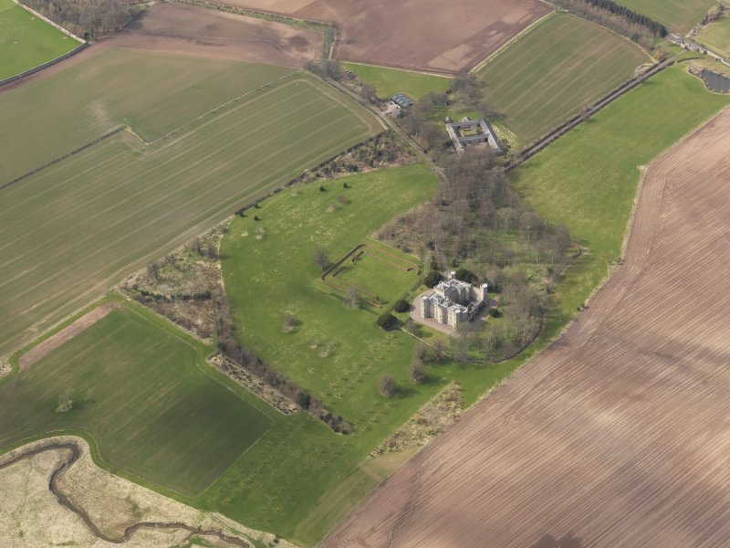 Oblique aerial view centred on the country house with the Home Farm adjacent,  taken from the SE.