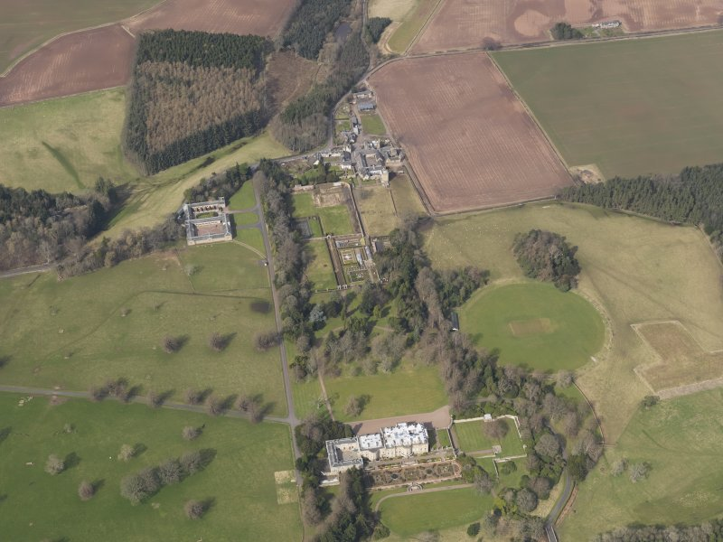Oblique aerial view centred on the country house with the formal garden adjacent, taken from the S.