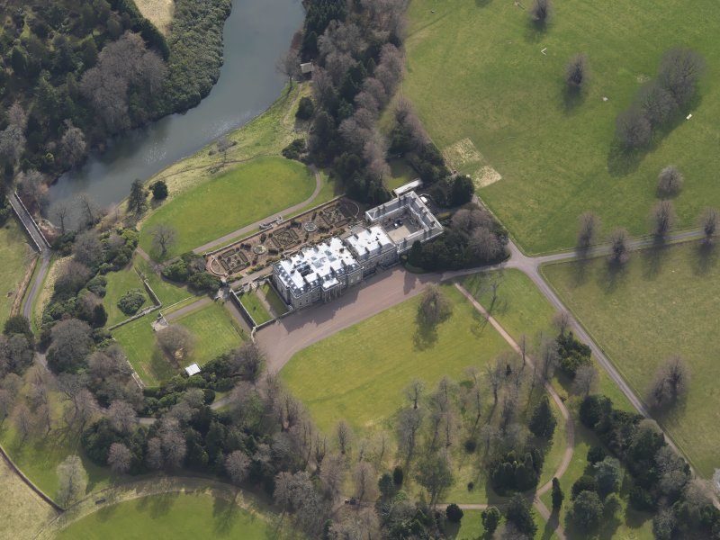 Oblique aerial view centred on the country house with the formal garden adjacent, taken from the N.