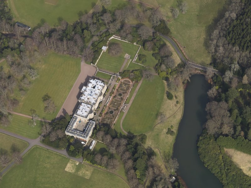 Oblique aerial view centred on the country house with the formal garden adjacent, taken from the SW.