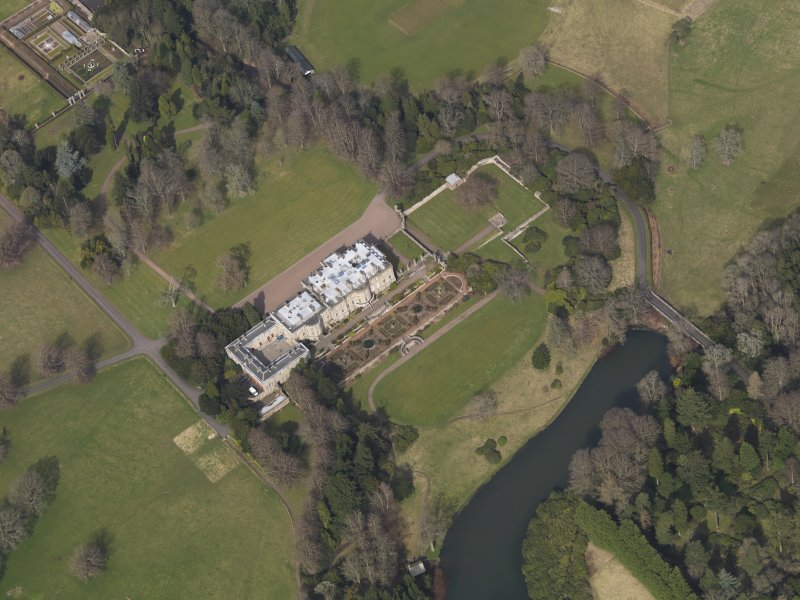Oblique aerial view centred on the country house with the formal garden adjacent, taken from the SSW.