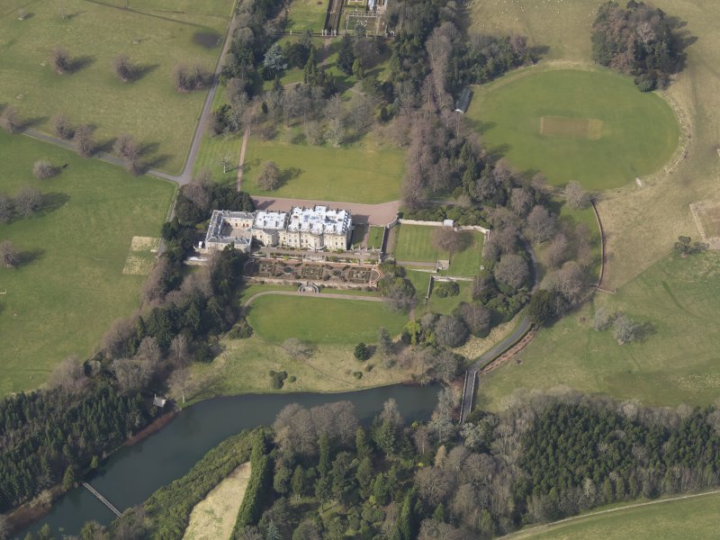 Oblique aerial view centred on the country house with the formal garden adjacent, taken from the SSE.