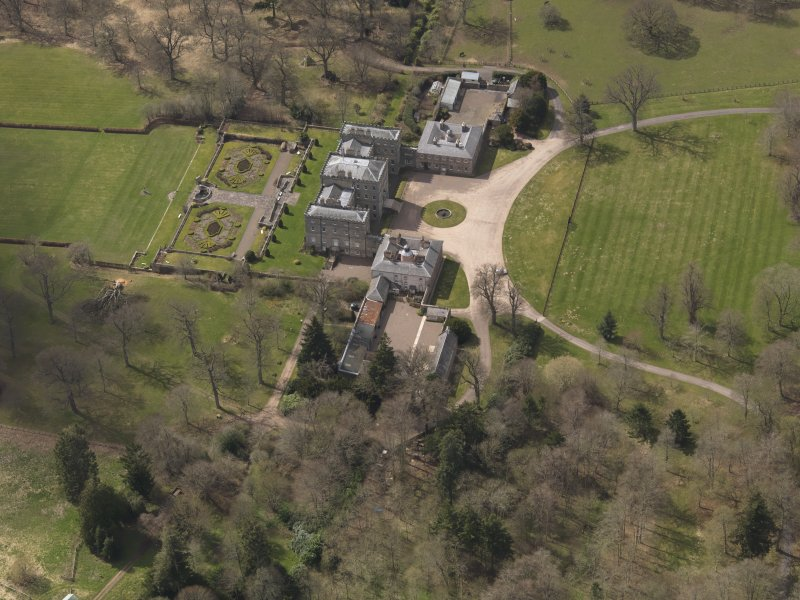 Oblique aerial view centred on the country house with the stable block adjacent, taken from the NE.