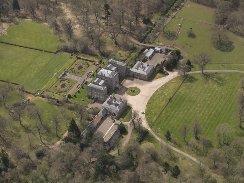 Oblique aerial view centred on the country house with the stable block adjacent, taken from the NNE.