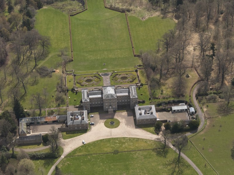 Oblique aerial view centred on the country house with the stable block adjacent, taken from the NNW.