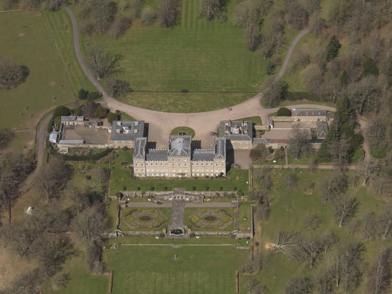 Oblique aerial view centred on the country house with the stable block adjacent, taken from the SE.