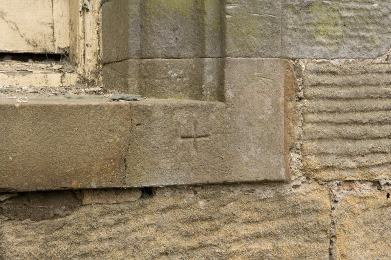 E facade, detail of incised cross mark on sill of ground floor window