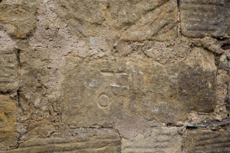 E facade, detail of incised cross and circular marks on ground floor level