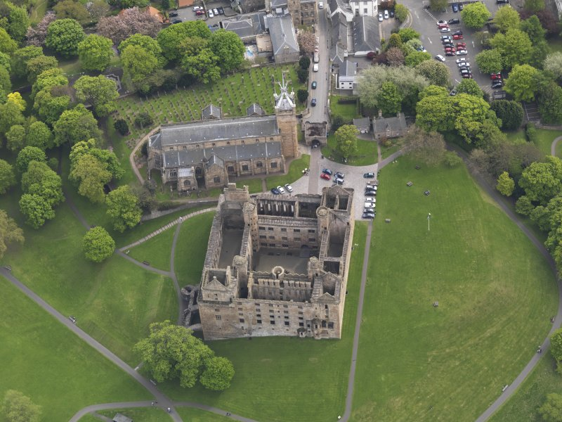 Oblique aerial view centred on the Palace with the parish church adjacent, taken from the N.