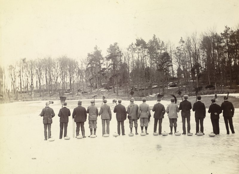 View of St Fort Curling Club on the ice with their backs to the camera.
