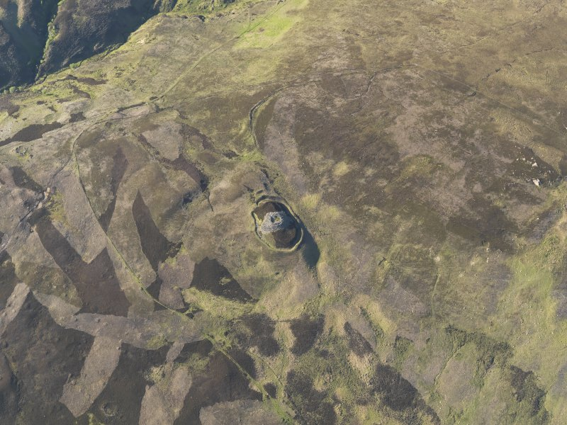 Oblique aerial view centred on Kilphedir Broch with the small cairns and hut-circles adjacent, taken from the S.