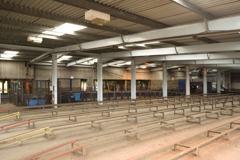 Interior. Cask preparation area with cask racking, view from SW. This is where casks were stored prior to loading onto the conveyor and being cleaned on their way to the Spirit Store to be filled.