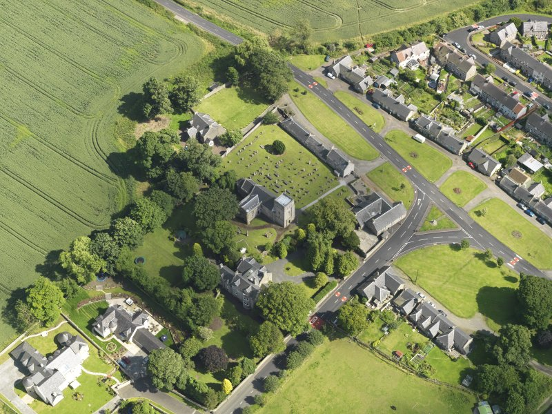 Oblique aerial view of Dalmeny centred on St Cuthbert's Church, taken from the NW.