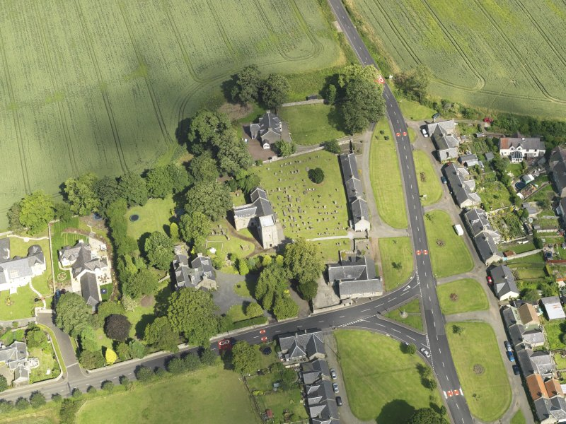 Oblique aerial view of Dalmeny centred on St Cuthbert's Church, taken from the W.