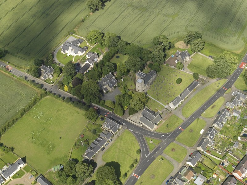 Oblique aerial view of Dalmeny centred on St Cuthbert's Church, taken from the SW.