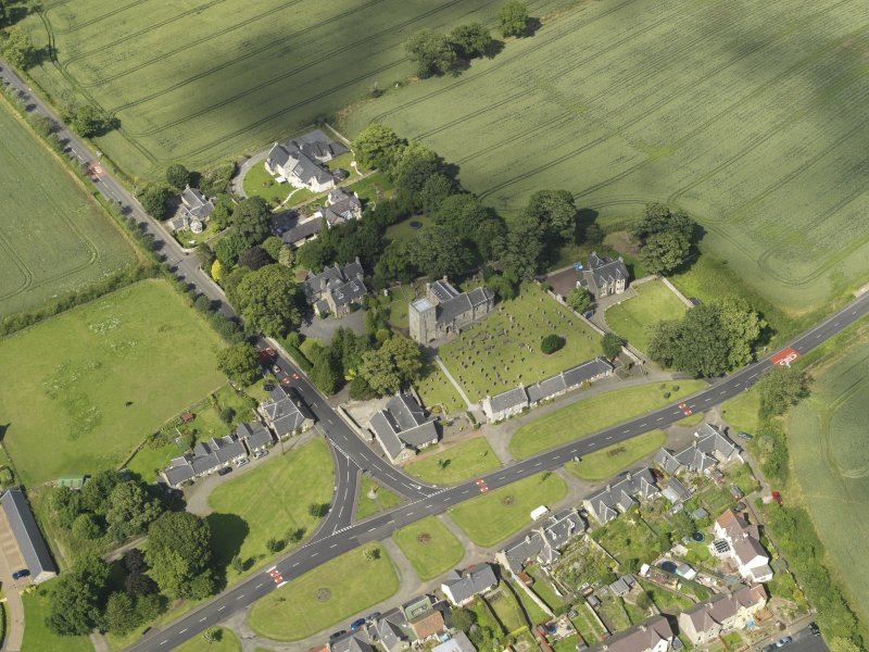 Oblique aerial view of Dalmeny centred on St Cuthbert's Church, taken from the SSW.