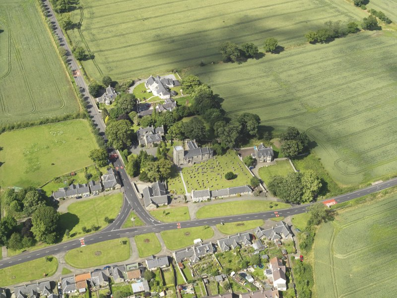 Oblique aerial view of Dalmeny centred on St Cuthbert's Church, taken from the S.