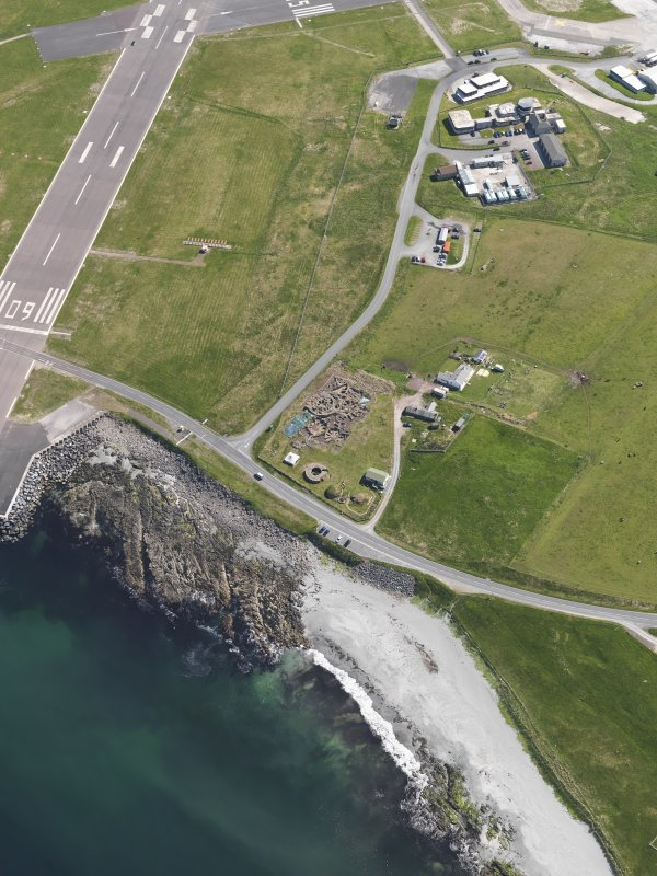 Oblique aerial view centred on the excavated broch and settlement at Old Scatness, Sumburgh, and the visitor attraction, taken from the WSW.
