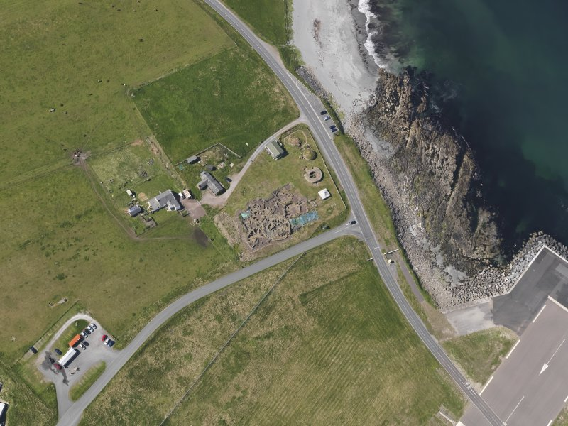 Oblique aerial view centred on the excavated broch and settlement at Old Scatness, Sumburgh, and the visitor attraction, taken from the NE.
