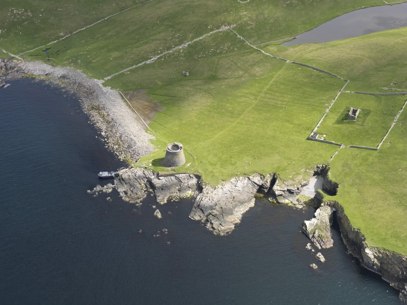 Oblique aerial view centred on the Broch of Mousa with The Haa and the burnt mound adjacent, taken from the SW.