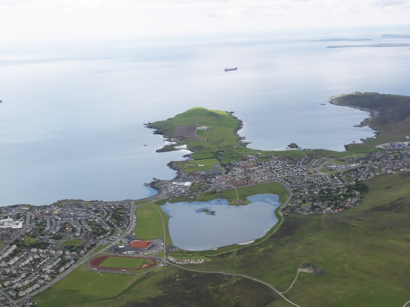 General oblique aerial view of the Loch of Clickimin with the Ness of Sound beyond, looking to the S.