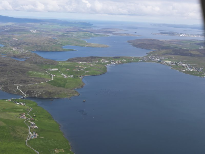 General oblique aerial view of Busta Voe and Brae village with Sullom Voe beyond, looking NNE.