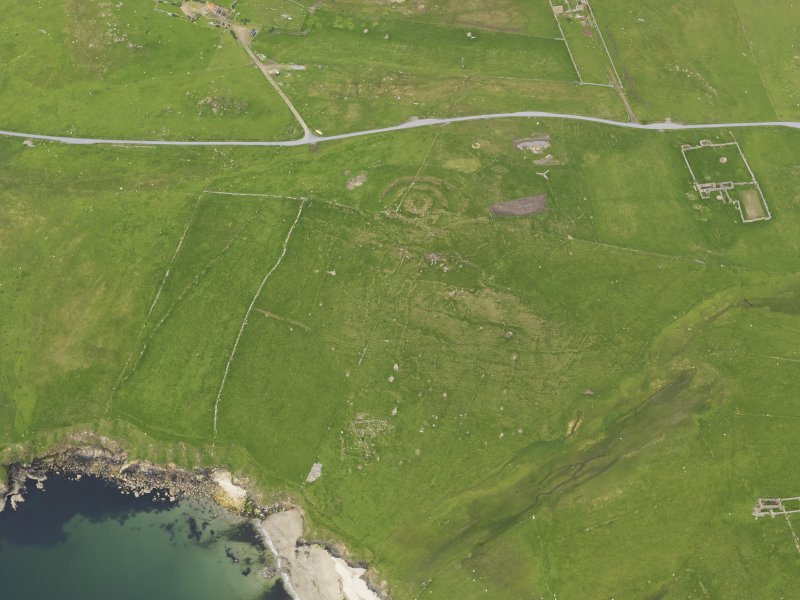 Oblique aerial view of the Broch of Underhoull and the field systems, looking ENE.