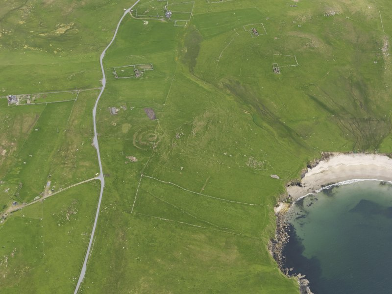 Oblique aerial view of the Broch of Underhoull and the field systems, looking SE.