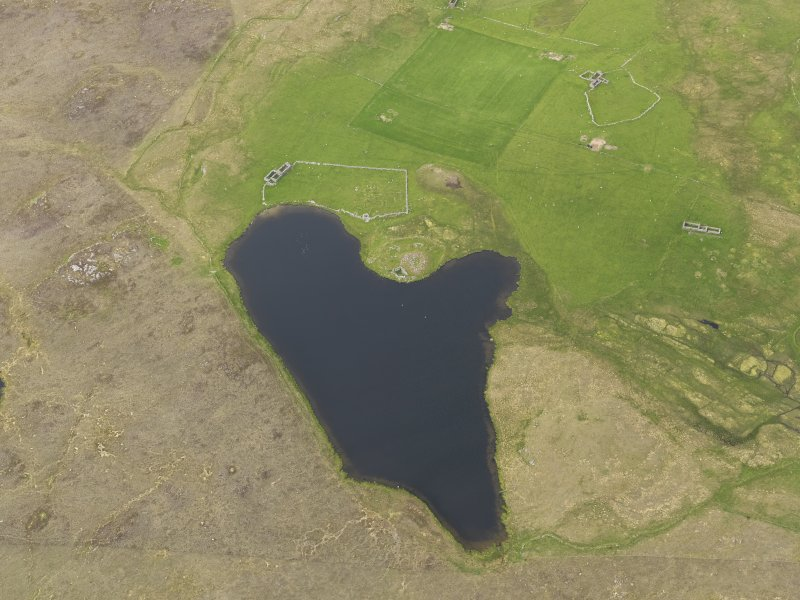 Oblique aerial view of the Loch of Snabrough Broch and the farmsteads, looking N.