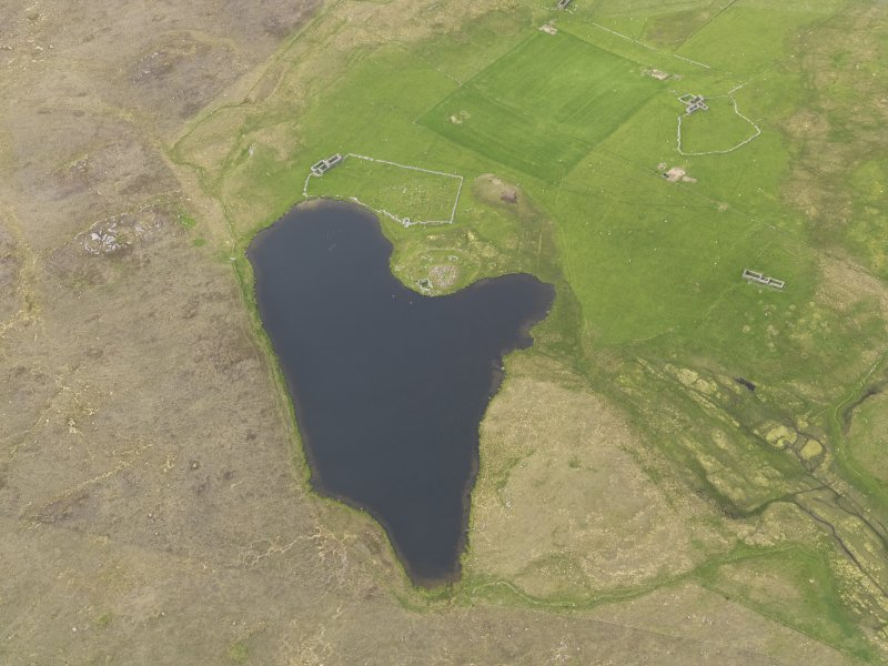 Oblique aerial view of the Loch of Snabrough Broch and the farmsteads, looking NNW.