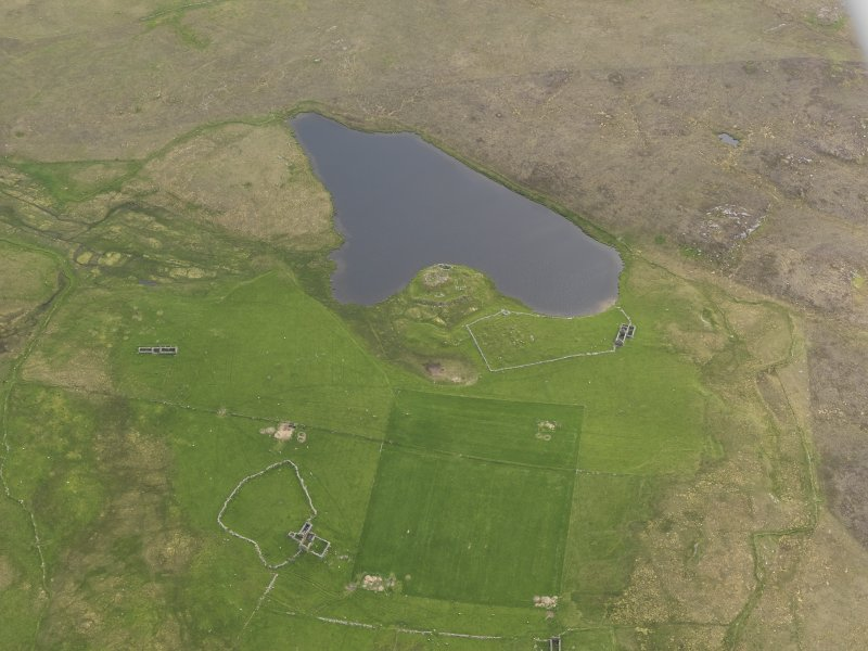 Oblique aerial view of the Loch of Snabrough Broch and the farmsteads, looking SW.