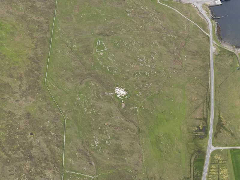 Oblique aerial view of the buildings and field systems, looking SSW.