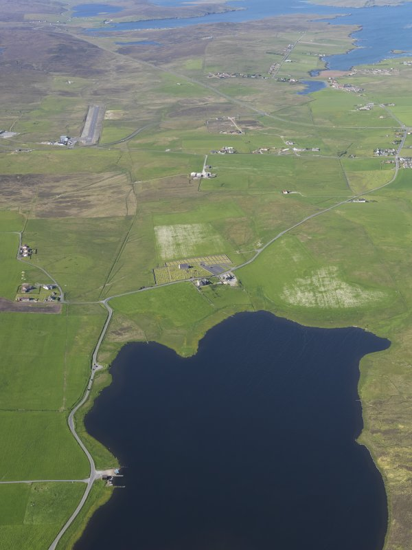 General oblique aerial view of the northern end of the Loch of Tingwall showing the Law Ting Holm with Veensgarth village and Tingwall Airport beyond, looking NNE.
