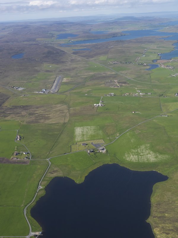 General oblique aerial view of the northern end of the Loch of Tingwall showing the Law Ting Holm with Veensgarth village and Tingwall Airport beyond, looking N.