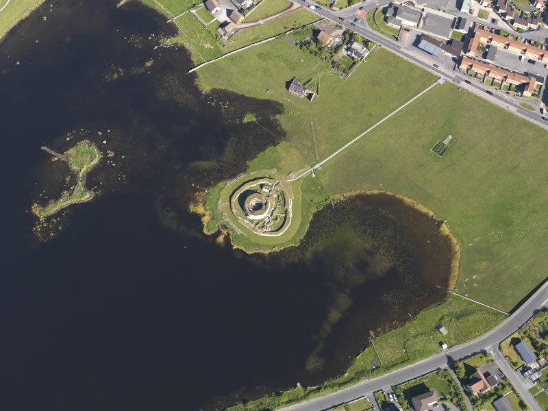 Oblique aerial view centred on the remains of the broch and settlement of Clickhimin, looking SE.