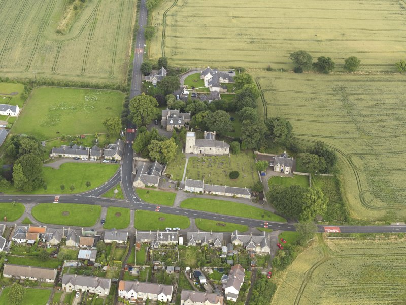 Oblique aerial view of Dalmeny centred on St Cuthbert's Church, taken from the SE.