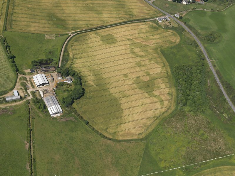 Oblique aerial view of the faint cropmarks of the barrow at Kirkmabreck, taken from the SSE.