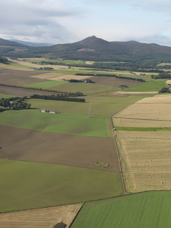 General oblique aerial view looking across the remains of Balquhain Recumbent Stone Circle with Mither Tap of Bennachie in the distance, taken from the E.