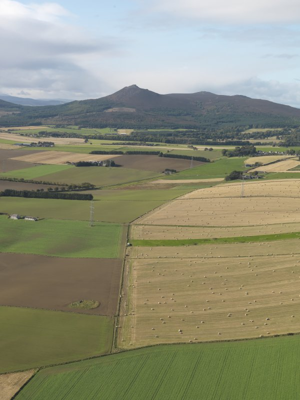 General oblique aerial view looking across the remains of Balquhain Recumbent Stone Circle with Mither Tap of Bennachie in the distance, taken from the ENE.