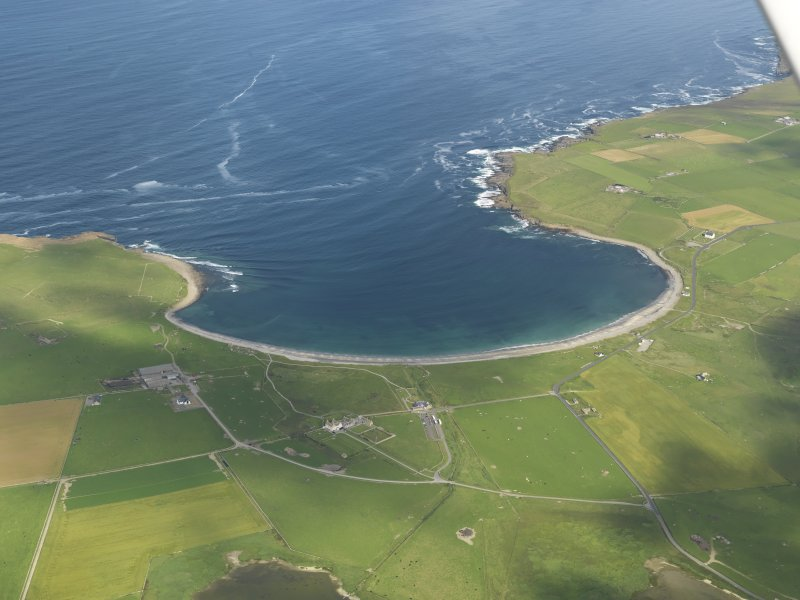 General oblique view of the Bay of Skaill with Skara Brae to the right and Skaill House adjacent, taken from the SE.