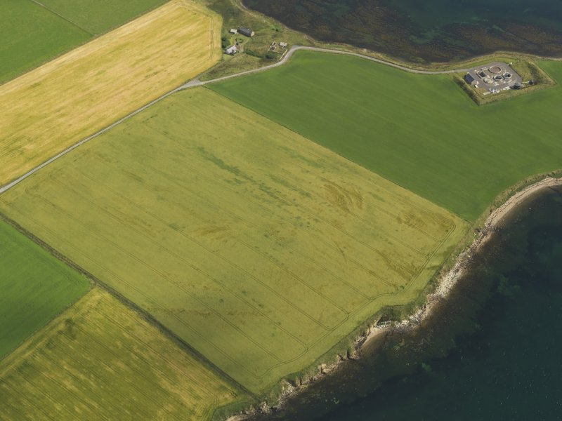 Oblique aerial view centred on the broch and souterrain at Bu, taken from the SW.