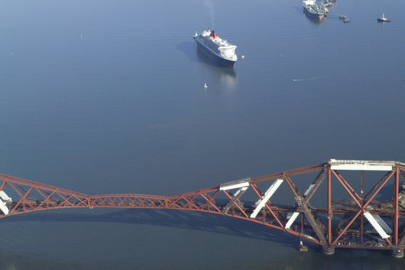 Oblique aerial view of the Queen Mary 2 with the Forth Rail Bridge in the foreground, taken from the WSW.