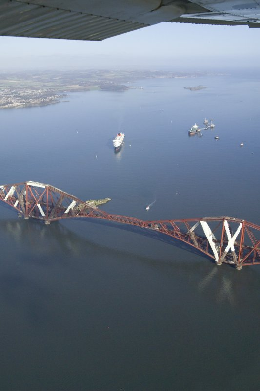 General oblique aerial view of the Queen Mary 2 with the Forth Rail Bridge in the foreground, taken from the SW.