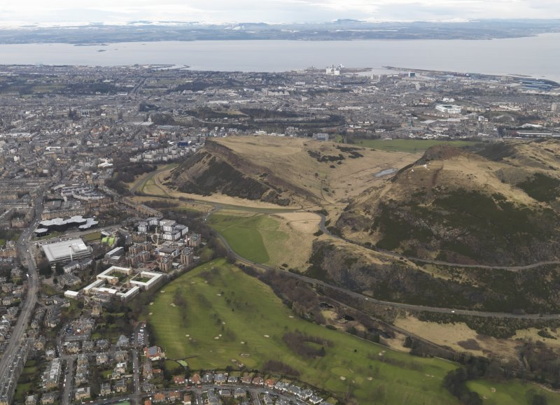 Oblique aerial view of Edinburgh centred on Holyrood Park and Salisbury Crags, taken from the SSE.