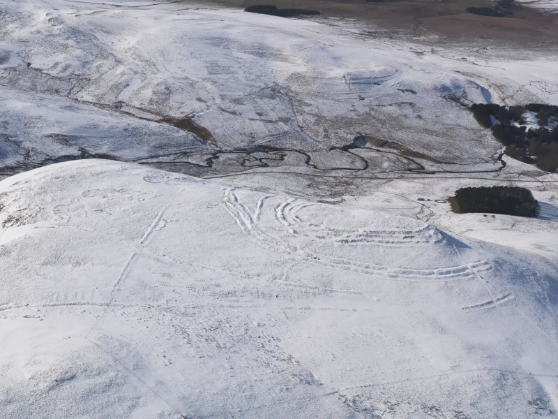 General oblique aerial view of Woden Law fort and linear earthworks in snow, looking WNW.