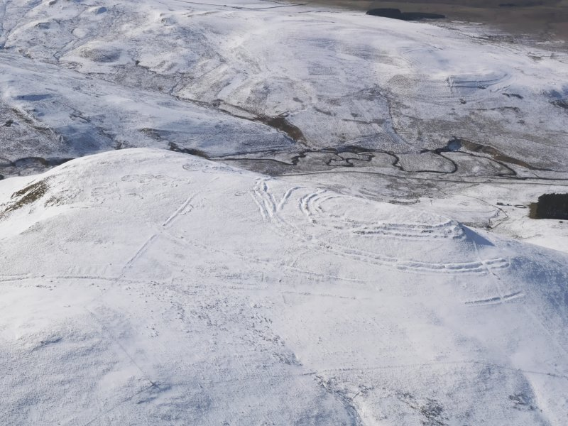 General oblique aerial view of Woden Law fort and linear earthworks in snow, looking W.